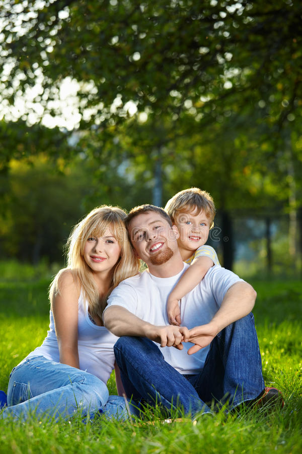 Happy family. Cheerful family with the small son have a rest on a lawn in a summer garden stock image