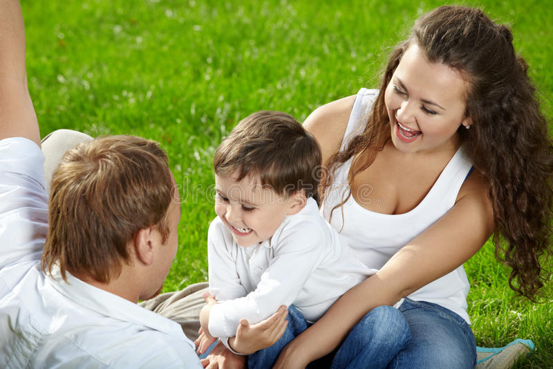 Happy family. Mother, father and small son have a rest in a summer garden royalty free stock image