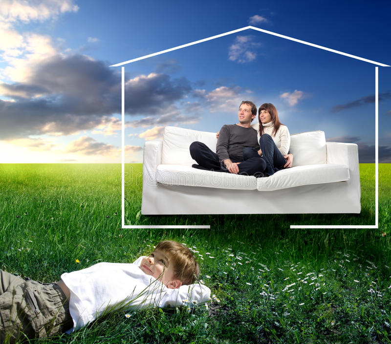 Happy family. Smiling child lying on a green meadow and smiling young couple sitting on a couch and surrounded by the form of a house