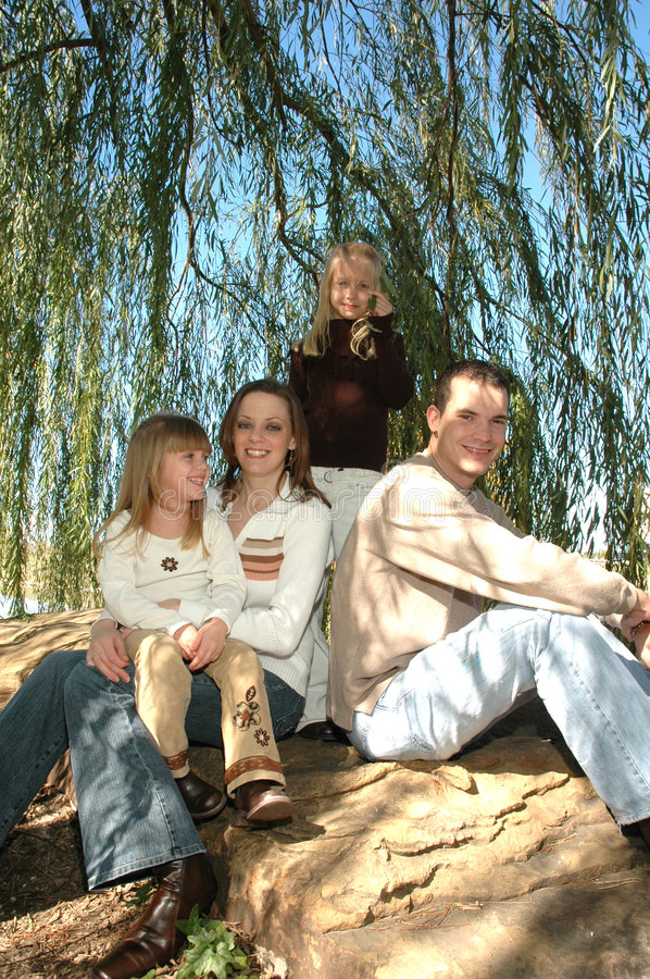 Happy Family. An american family take their portraits in nature sitting outside on a big rock under a weeping willow tree. A family of four with two daughters royalty free stock photo