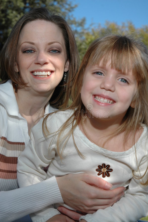 Happy Family. A cute little four year old girl and her mommy pose together. Spending time together with mom and daughter. Mother hugs her little girl close to royalty free stock photos