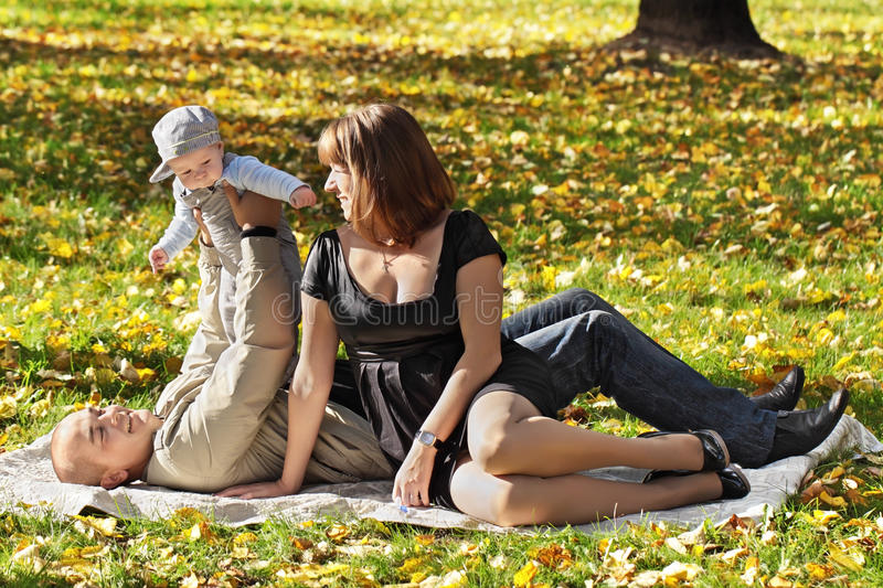 Happy family. Young man and the woman play with the child in park a grass