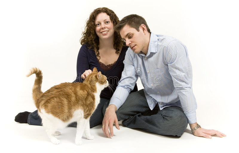 Happy Family. Young couple spends time playing with their pet cat stock image