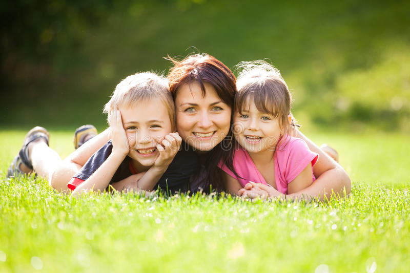 Happy family. Outdoors on the grass in a park, smiling faces all lying down having fun stock images