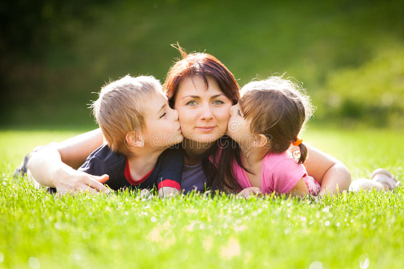 Happy family. Outdoors on the grass in a park, smiling faces all lying down having fun stock photos