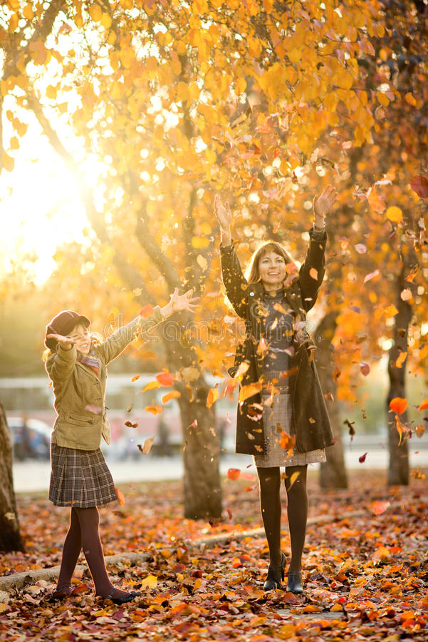 Happy family. Vertical photo, happy beautiful little girl with mather throw up autumnal leafage, in park. Focus on little girl stock photos