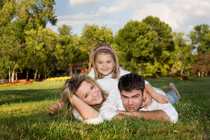Happy family. Daugnter, mother and father playing outside on a sunny day stock image