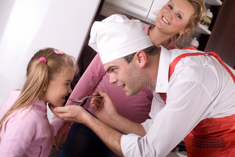 Happy family. Father is prepraing lunch for his family stock photography