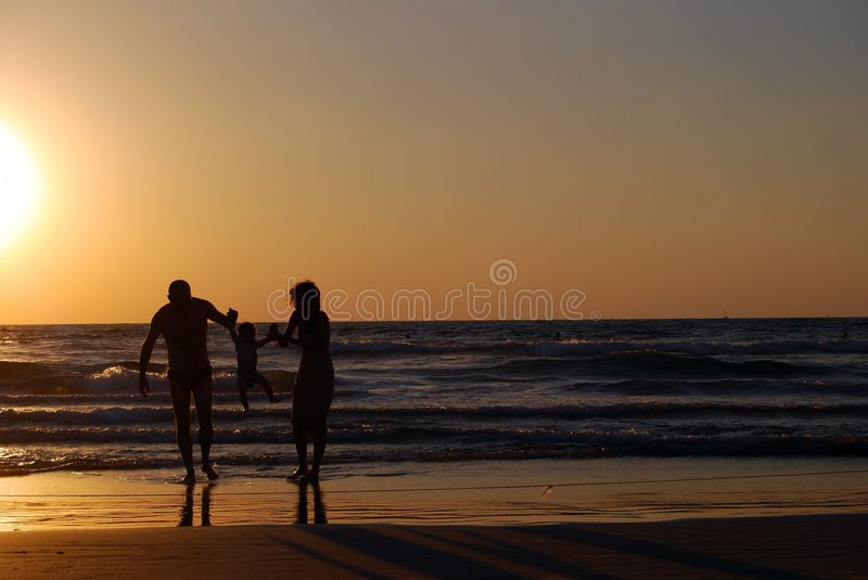 Happy family. On the sea beach at the moment of sunset stock photos
