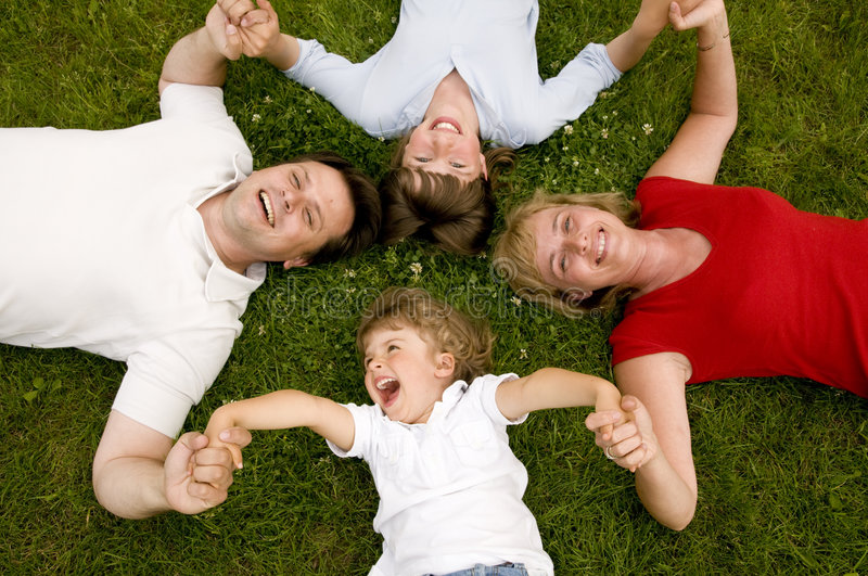 Happy family. Parents with kids laying on the grass