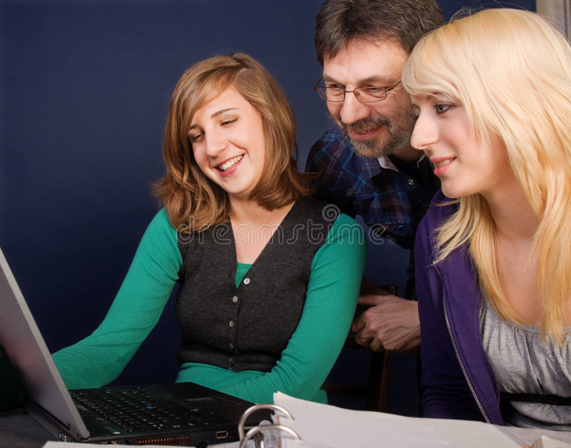 Happy family. Smiling teenager girls and their father looking at laptop screen