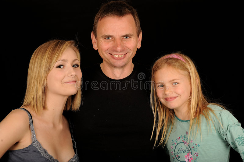 Happy family. Half body portrait of smiling father with teenage and young daughter, isolated on black background royalty free stock photography