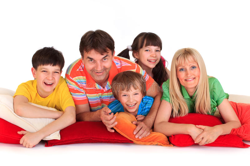 Happy family. Close up of happy family lying on red bolster cushions with white background stock photos