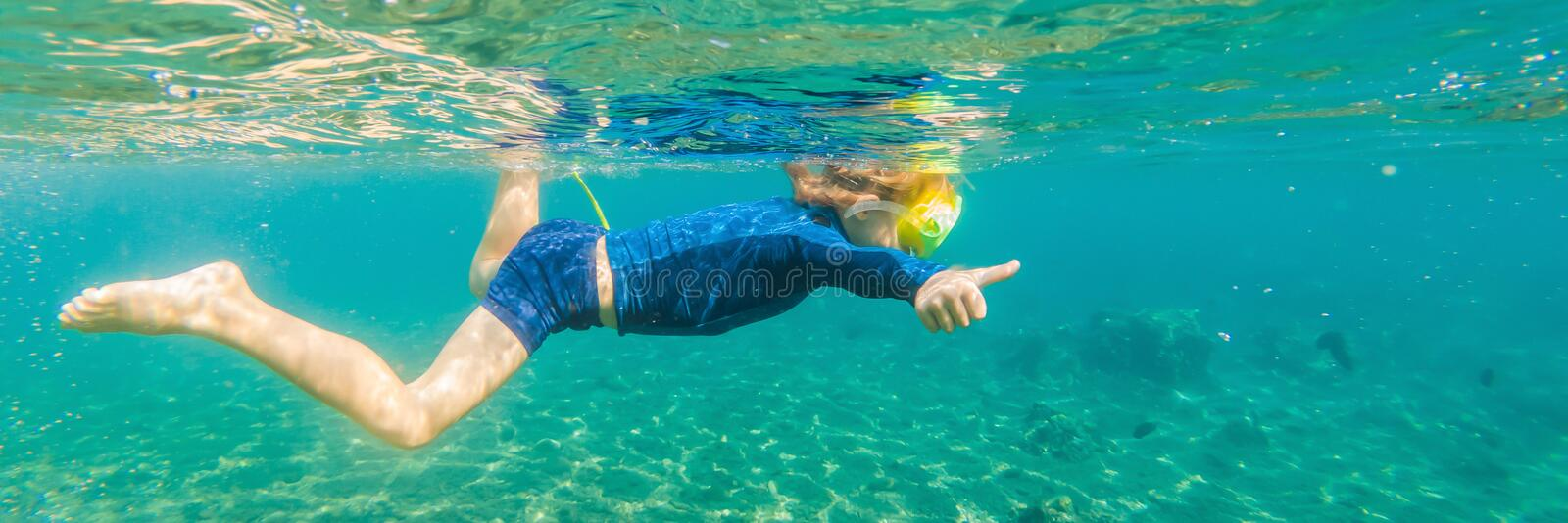 Happy family - active kid in snorkeling mask dive underwater, see tropical fish in coral reef sea pool. Travel adventure royalty free stock images