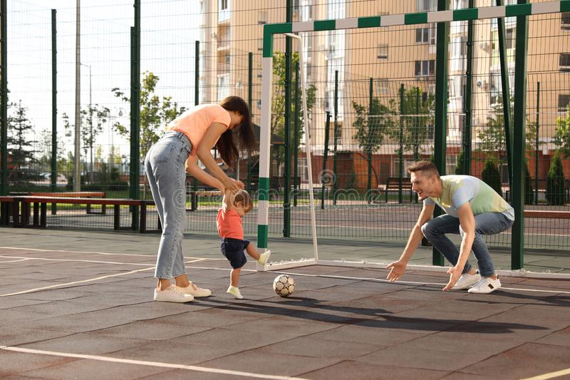 Happy family with adorable little baby playing football stock image