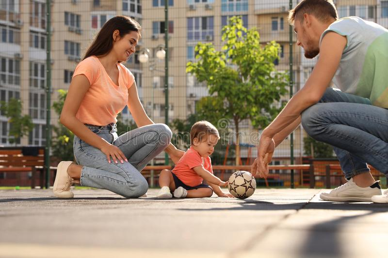 Happy family  adorable little baby playing football outdoors stock images