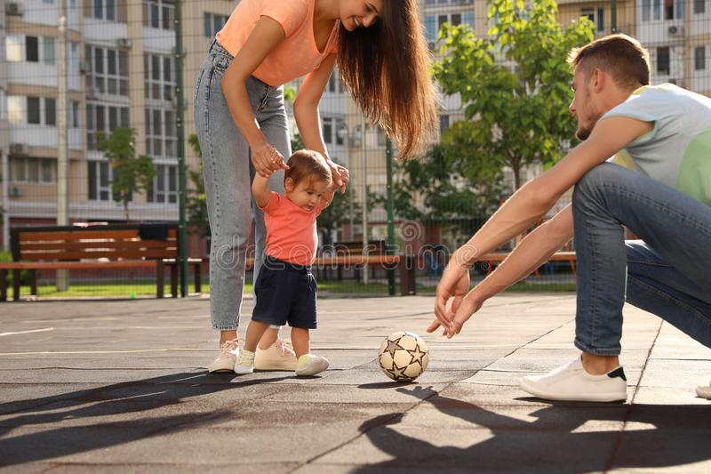 Happy family = adorable little baby playing football outdoors royalty free stock image