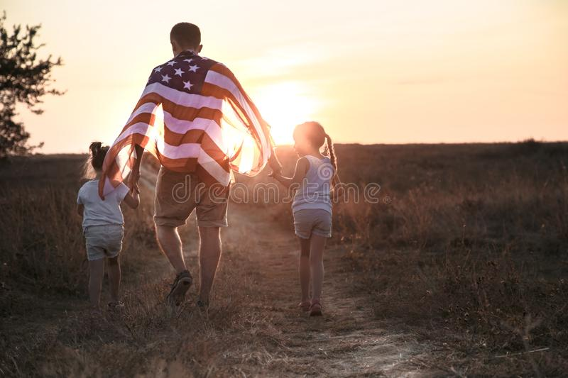 A happy family with an American flag at sunset. Happy family, dad and daughter holding the American flag at sunset. Dressed in white. The concept of family stock image