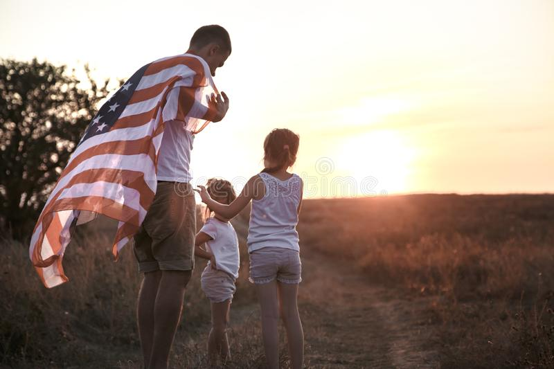 A happy family with an American flag at sunset. Happy family, dad and daughter holding the American flag at sunset. Dressed in white. The concept of family royalty free stock images