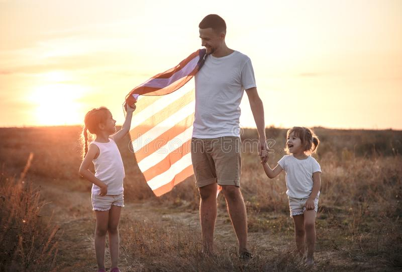 A happy family with an American flag at sunset. Happy family, dad and daughter holding the American flag at sunset. Dressed in white. The concept of family stock images