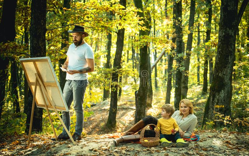 Happy family. Artist father Drawing own Family from nature. with a beard in a hat, creating a canvas. Artist services stock images