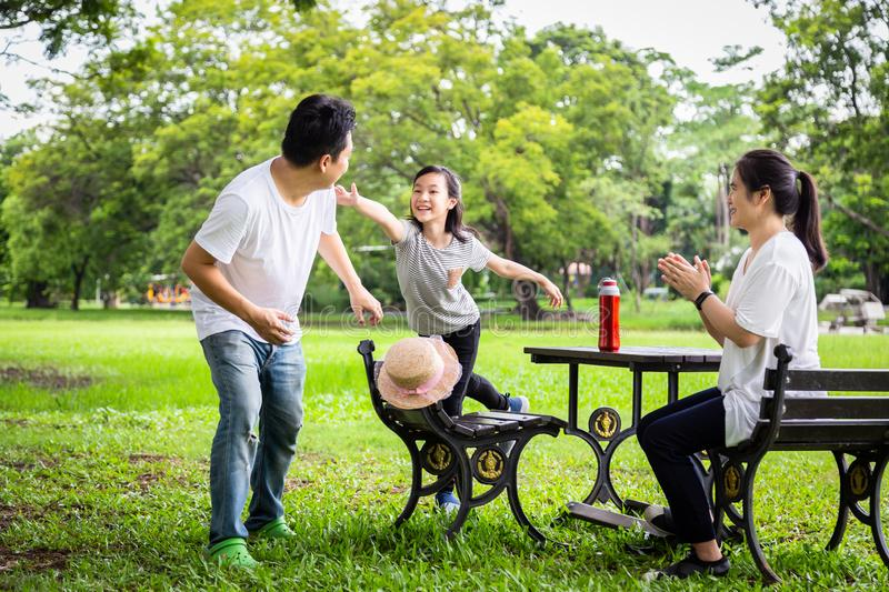 Happy family,asian little child girl or daughter playing tag game,running joyful with father and mother in summer green nature,dad stock photos