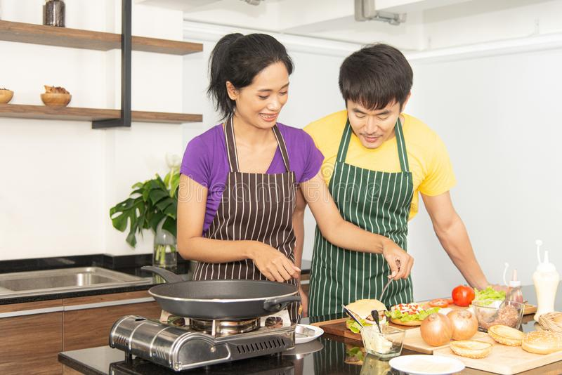 Happy family. Asian lovely couple, beautiful woman and handsome man preparing ingredients and cooking food for having breakfast stock photography