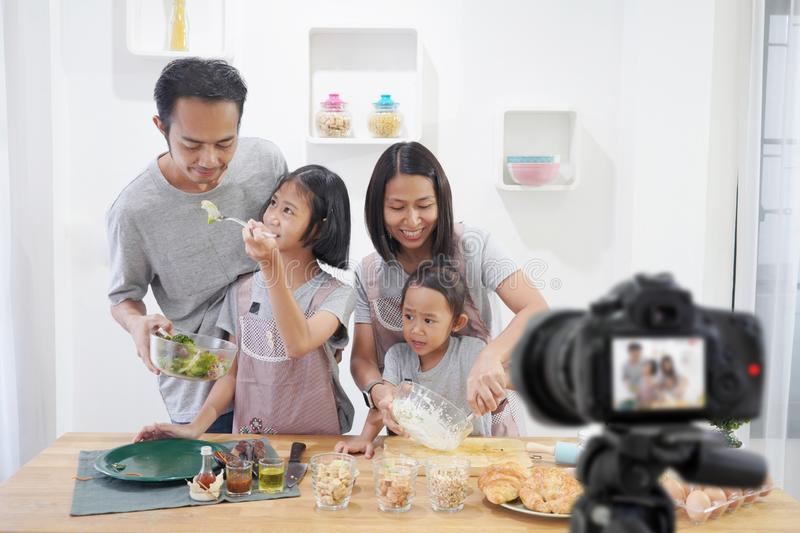Happy family asian making a Vlog video blogger digital camera with cooking royalty free stock images