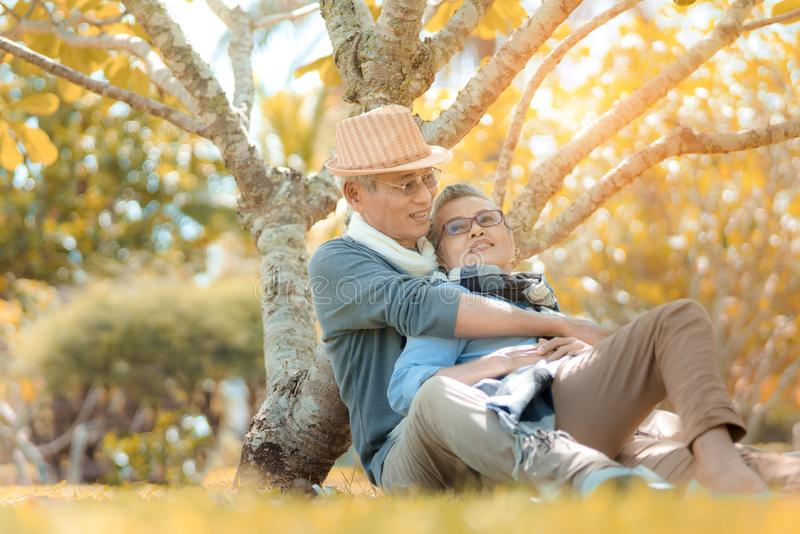 Happy family asian senior couple retirement sitting and hugging smile in nature stock photo