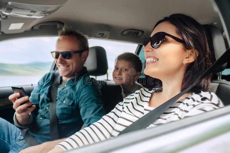 Happy family auto traveling concept image. Car interior view of female driving, man dealing mobile phone and little son smiling. Happy family auto traveling stock photo