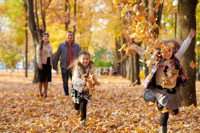 Happy family is in autumn city park. Children and parents running with leaves.. They posing, smiling, playing and having fun. royalty free stock images