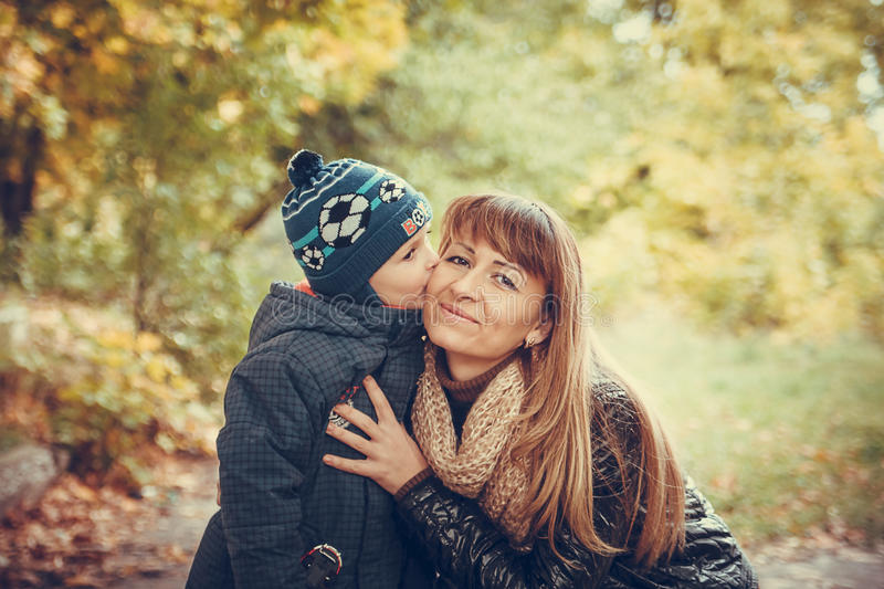 Happy family in autumn forest photo. Picture of Son kiss his mother in the autumn forest stock image