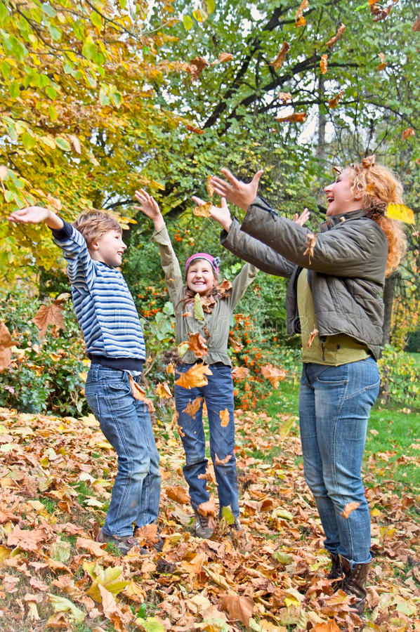 Happy family in autumn forest play with fallen leaf royalty free stock image
