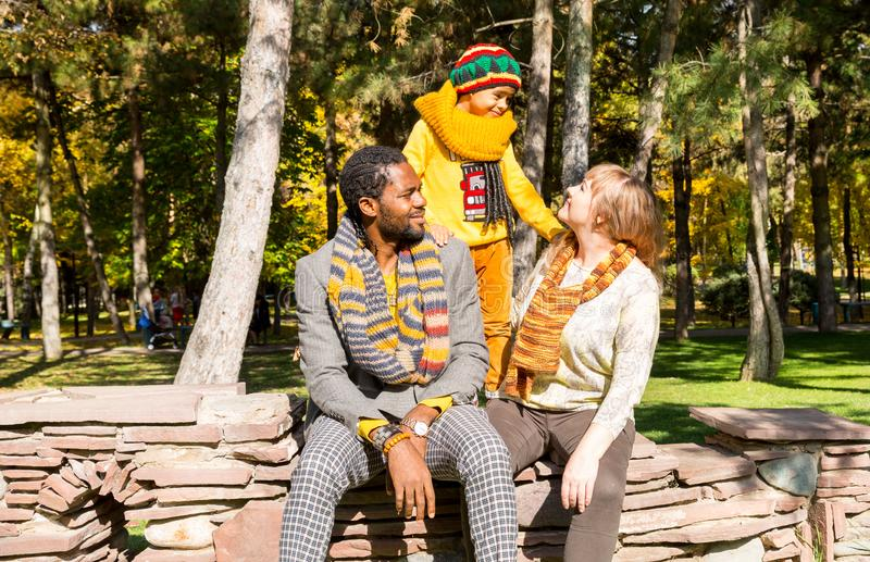 Happy family in autumn park. African American family: black father, mom and child boy on nature in fall. Happy family in autumn park. African American family royalty free stock photo