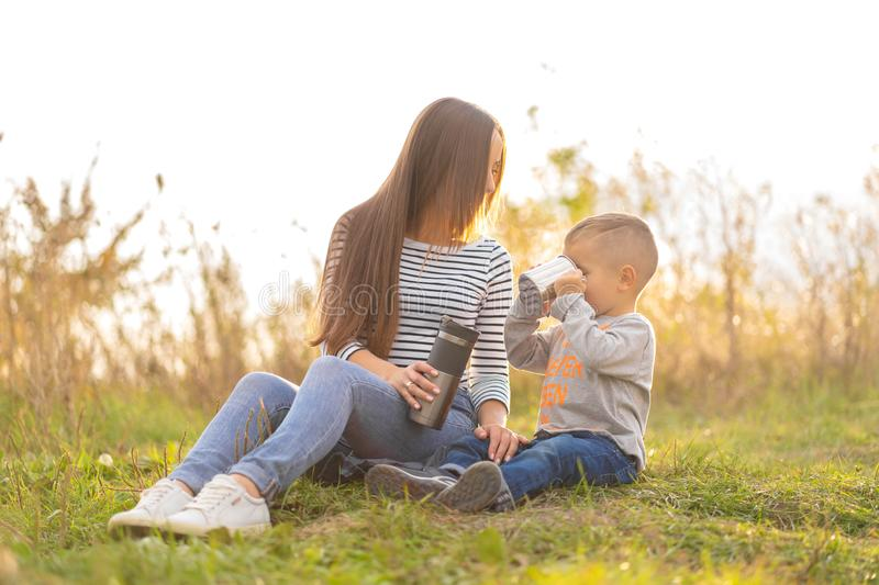 Happy family on autumn walk. Young beautiful mother with little son enjoy nature royalty free stock images