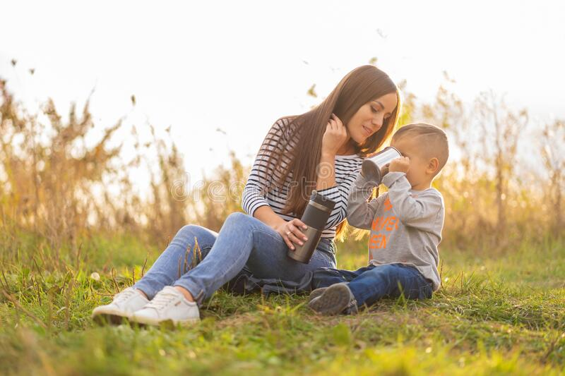 Happy family on autumn walk. Young beautiful mother with little son enjoy nature stock photography