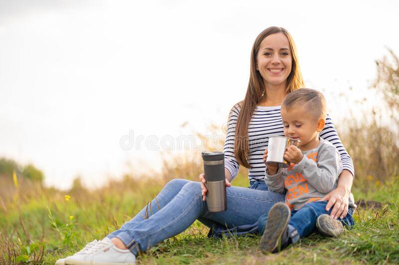 Happy family on autumn walk. Young beautiful mother with little son enjoy nature royalty free stock photos