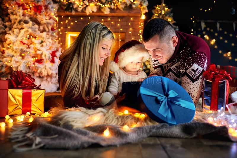 Happy family with a baby in a Christmas room. Happy family with a baby in a Santa Claus hat in a Christmas room in Christmas day royalty free stock photo