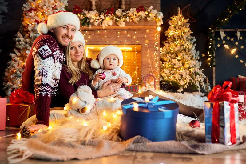 Happy family with a baby in a Christmas room. Happy family with a baby in a Santa Claus hat in a Christmas room in Christmas day stock photo