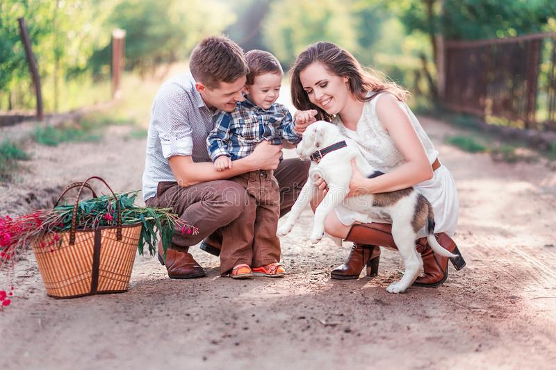Happy family with baby and little puppy royalty free stock photography