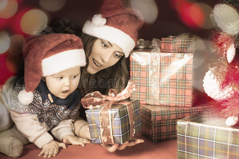 Happy family of baby and mother near the Christmas tree royalty free stock image