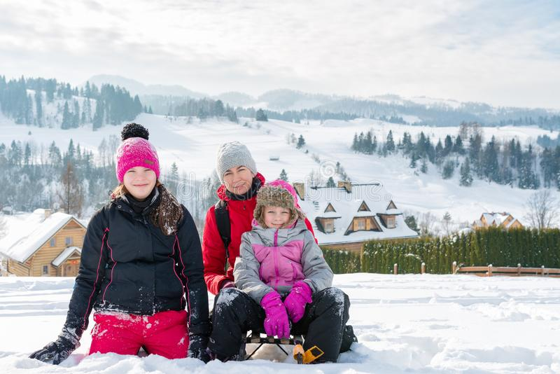 Happy family on the background of a winter mountain landscape - mom and daughters on a snowy hillside in Pieniny mountains. Happy family on the background of a stock images