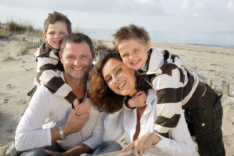 Happy family on the beach. Beautiful family of four sitting on the beach royalty free stock photo