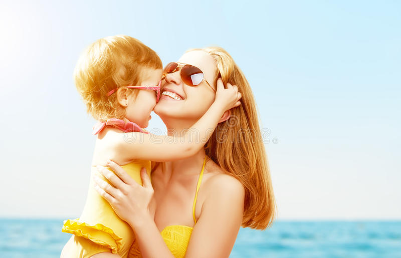 Happy family on beach. baby daughter kissing mother stock image