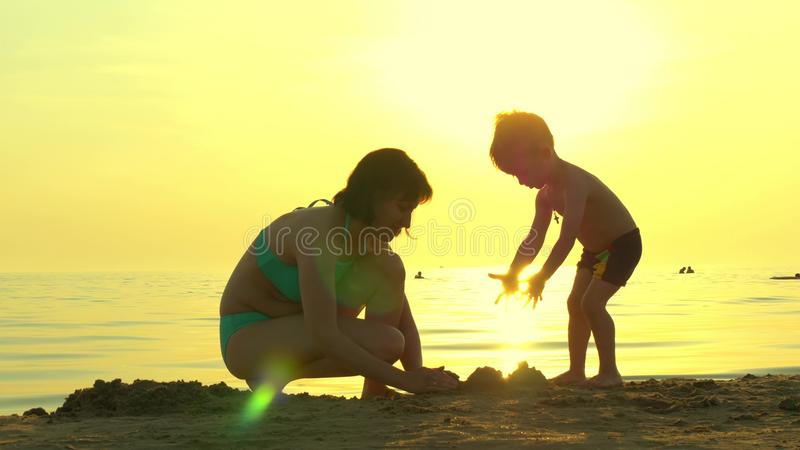 Happy family on the beach. Mom and child build a sand castle against the backdrop of the sea sunset. The concept of a stock photography