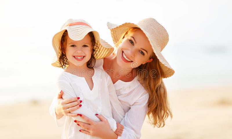 Happy family at beach. mother and child daughter hug at sunset royalty free stock image