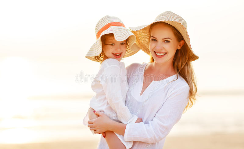 Happy family at beach. mother and child daughter hug at sunset royalty free stock photo