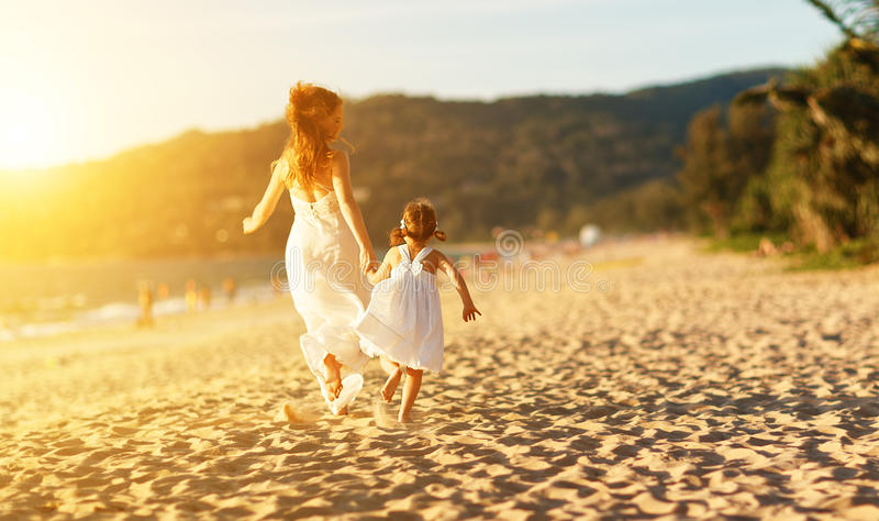 Happy family at beach. mother and child daughter run, laugh and. Happy family at the beach. motherand child daughter run, laugh and play at sunset royalty free stock image