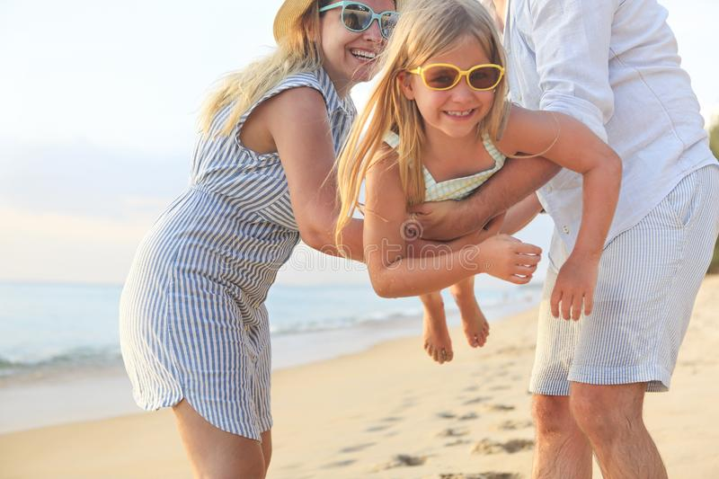 Happy family on the beach. People having fun on summer vacation. Father, mother and child against blue sea and beach background royalty free stock photo