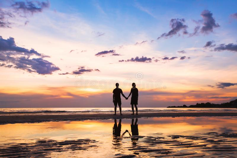 Happy family on the beach, silhouette of couple at sunset, man and woman royalty free stock photography